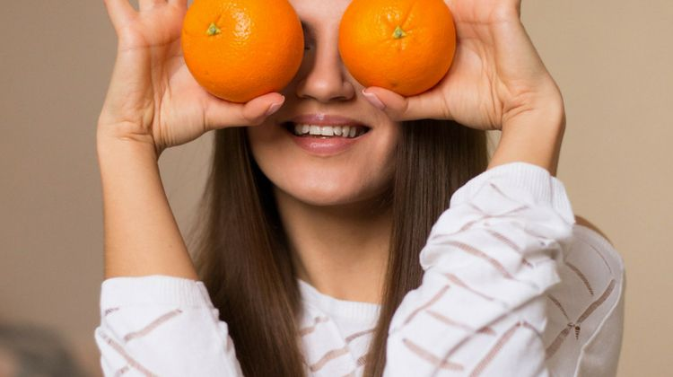 girl holding oranges to face